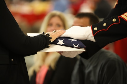 Staff Sgt. Christian Wolanski, a recruiter at Recruiting Station St. Louis, delivers a flag to a Gold Star mother at the 7th Annual Gold Star Family Luncheon Oct. 1, 2016 in St. Louis, Mo. The term Gold Star refers to a family who lost a loved one in war. (U.S. Marine Corps photo by Cpl. Jennifer Webster/Released)