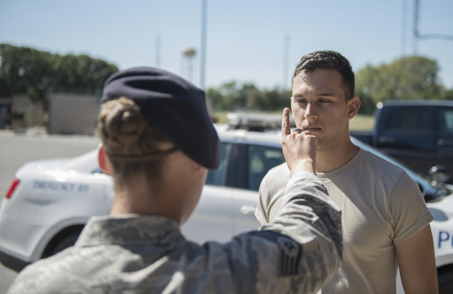 U.S. Air Force Staff Sgt. Devin Pope, 509th Security Forces Squadron (SFS) training instructor, left, demonstrates the Horizontal Gaze Nystagmus (HGN) test with Airman 1st Class John Cabral, 509th SFS member, at Whiteman Air Force Base, Mo., Sept. 30, 2016. As part of Standard Field Sobriety Test used by SFS when a driver is suspected of driving under the influence of alcohol or drugs, patrolmen carry out HGN tests during which they check a driver's eyes for indications of impairment. (U.S. Air Force photo by 1st Lt. Matthew Van Wagenen)
