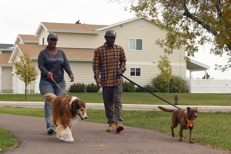 Capt. Brittany Rhanes, 341st Operations Support Squadron intercontinental ballistic missile emergency war order planner, and her husband Anthony, walk their dogs Oct. 5, 2016, at Malmstrom Air Force Base, Mont. Rhanes was diagnosed with vulvar cancer Feb. 17, 2016, and made a promise to not let that stop her. (U.S. Air Force photo/Senior Airman Jaeda Tookes)