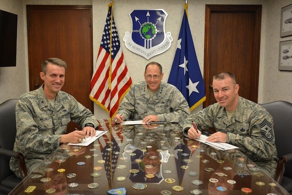 """On Oct. 7, Air Force Sustainment Center senior leaders take time to fill in their pledge cards to signal the start of the Combined Federal Campaign, which began Oct. 3 and runs through Nov. 17. Filling in their pledge cards are Lt. Gen. Lee K. Levy II, AFSC commander, center, Brig. Gen. Tom Miller, AFSC vice commander, left, and AFSC Command Chief Master Sgt. Gary Sharp. The CFC is one of only two official fundraisers approved each year for Department of Defense employees. This year's theme is """"Camp CFC – Let the CAMPaign Begin."""" (Photo by Darren D. Heusel)"""