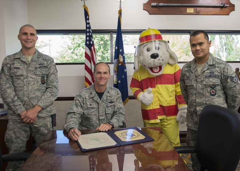 (From the left) Staff Sgt. Tyler Ford, 366th Civil Engineer Squadron firefighter; Col. Jefferson O'Donnell, 366th Fighter Wing commander; Sparky the Dog; and Staff Sgt. Francis Abac, 366th CES firefighter, gather to proclaim Fire Prevention Week at Mountain Home Air Force Base, Idaho, Oct. 7, 2016. National Fire Prevention Week was created in 1925 by president Calvin Coolidge to help prevent fire deaths and memorialize the Chicago Fire of 1871 which killed more than 250 people. (U.S. Air Force photo by Airman 1st Class Chester Mientkiewicz/Released)