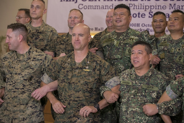 U.S. and Philippine Marines interlock arms in solidarity during the Philippine Amphibious Landing Exercise 33 (PHIBLEX) opening ceremony at Marine Barracks Rudiardo Brown, Taguig City, Philippines, Oct. 4, 2016. PHIBLEX is an annual U.S.-Philippine military bilateral exercise which combines amphibious capabilities and live-fire training with humanitarian civic assistance efforts to strengthen interoperability and working relationships. The U.S. Marines are with 3d Marine Expeditionary Brigade, III Marine Expeditionary Force. (U.S. Marine Corps photo by Cpl. Steven Tran/Released)