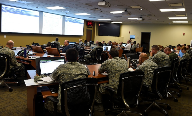 Mission essential personnel discuss ongoing operations at the Emergency Operations Center during Hurricane Condition I for Hurricane Matthew on Joint Base Charleston, S.C., Oct. 7, 2016. All non-essential personnel evacuated the area, but will return after disaster response coordinators assess damage and verify a safe operating environment. (U.S. Air Force photo by Senior Airman Nicholas Byers)