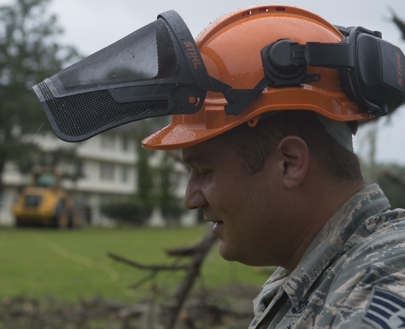 U.S. Air Force Staff Sgt. Scott Cross, a pavement and equipment craftsman assigned to the 628th Civil Engineer Squadron, takes a breath after felling a dead tree ahead of Hurricane Matthew at Joint Base Charleston, S.C., Oct. 7, 2016. All non-essential personnel evacuated the area, but will return after disaster response coordinators assess damage and verify a safe operating environment. (U.S. Air Force photo by Tech. Sgt. Barry Loo)
