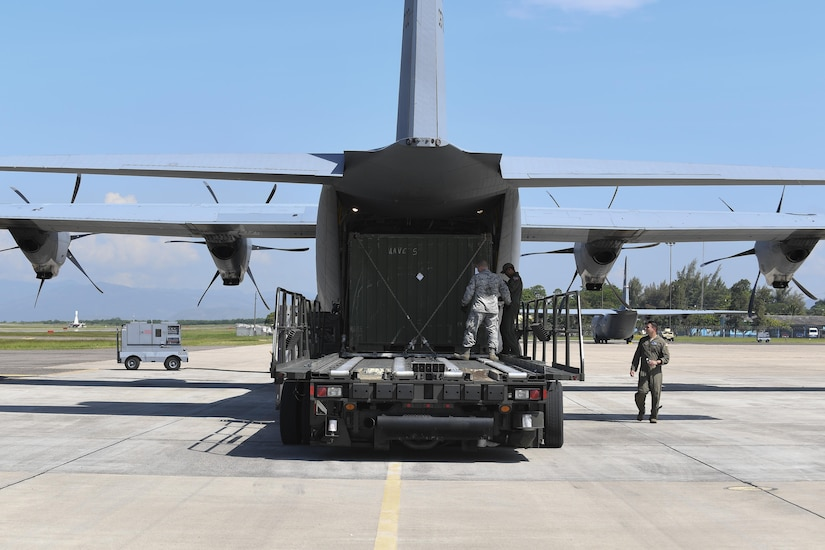 """U.S. Air Force Staff Sgt. Dustin Jett, 612th Air Base Squadron senior information controller, helps aircrew members from Dyess Air Force Base, Texas load a """"conex"""" box onto a C-130J Hercules at Soto Cano Air Base, Honduras, Oct. 7, 2016. U.S. Southern Command requested heavy airlift to transport critical equipment packages needed to sustain helicopter flight operations in Haiti being conducted by Special Purpose Marine Air-Ground Task Force-Southern Command and Joint Task Force-Bravo's 1st Battalion, 228th Aviation Regiment using two CH-53E Super Stallions, three CH-47 Chinooks, and two UH-60L and two HH-60L Black Hawks in support of the U.S. Agency for International Development-led mission to alleviate human suffering and bolster Haitian disaster response capabilities."""