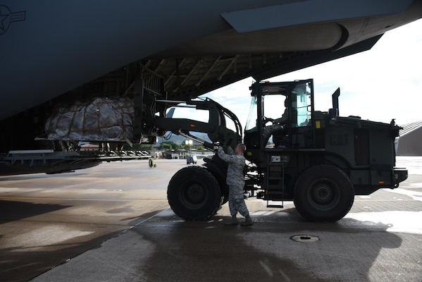 U.S. Air Force Staff Sgt. Dustin Jett, 612th Air Base Squadron senior information controller, guides a forklift driven by U.S. Air Force Staff Sgt. Jordan Woodard, 612th ABS information controller, into a C-17 Globemaster III cargo aircraft at Soto Cano Air Base, Honduras, with equipment destined for Port-au-Prince, Haiti to support Joint Task Force Matthew hurricane relief operations, Oct. 8, 2016. Extensive joint planning between Special Purpose Marine Air-Ground Task Force-Southern Command and JTF-Bravo logistics personnel was required to establish load plans and cargo prioritization so the equipment would be ready to load and transport without delay to prevent any mission stoppages or shortfalls. (U.S. Air Force photo by Capt. David Liapis)