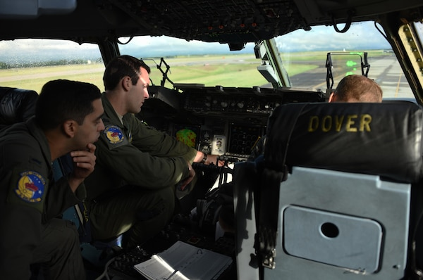 U.S. Air Force 1st Lt. Ben Bertelson, observes as U.S. Air Force Capt. Mike Kieffabar, both 3rd Airlift Squadron pilots, reviews the final mission plan for their flight to Port-au-Prince, Haiti from Soto Cano Air Base, Honduras, Oct. 8, 2016. The aircraft and crew from Dover Air Force Base, Delaware, deployed to Soto Cano within hours of being requested by U.S. Southern Command to transport additional personnel and equipment necessary to sustain flight and maintenance operations for to support Joint Task Force Matthew hurricane relief operations where approximately 200 Soldiers, Airmen and Marines from Special Purpose Marine Air-Ground Task Force-Southern Command and Joint Task Force-Bravo deployed this week with two CH-53E Super Stallion, three CH-47 Chinook, and two UH-60L and two HH-60L Black Hawk helicopters to provide heavy and medium lift to support the U.S. Agency for International Development-led mission. (U.S. Air Force photo by Capt. David Liapis)