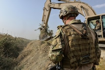 Capt. Erik Blum watches as Master Sgt. Thomas Ryan removes reeds from a 7-meter deep trench at Kabul Air Wing, Afghanistan, Oct. 6, 2016. The Train, Advise, Assist Command-Air (TAAC-Air) civil engineer advisors worked to clear a field of reeds in excess of 15-feet tall. The height of the vegetation had become a force protection concern for security forces personnel manning an entry control point who couldn't properly see past the field. (U.S. Air Force photo by Tech. Sgt. Christopher Holmes)