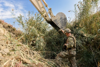 Capt. Erik Blum, Train, Advise, Assist Command-Air (TAAC-Air) civil engineer advisor, directs an excavator from a trench during a field clearing mission at Kabul Air Wing, Afghanistan, Oct. 6, 2016. Civil engineer advisors took on the project to clear a field of reeds that had grown to an excess of 15 feet, preventing security forces members manning an entry control point from being able to properly view the surrounding area.