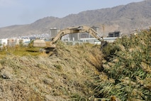 Civil engineer advisors from Train, Advise, Assist Command-Air (TAAC-Air) clear a field surrounding an entry control point at Kabul Air Wing, Afghanistan, Oct. 6, 2016. The team cleared an area of 350-meters long, 20-meters wide, and 7-meters deep of reeds that had grown in excess of 15 feet.