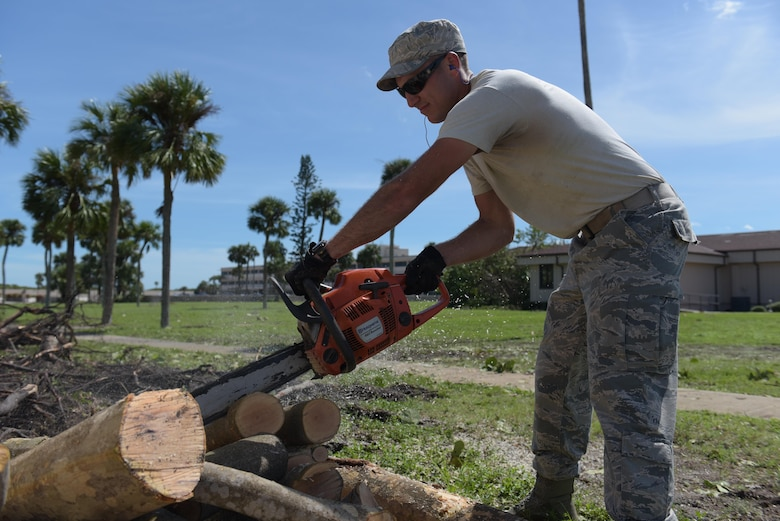Staff Sgt. Micky Stoner, of the 45th Civil Engineer Squadron, cuts limbs of fallen trees during the 45th Space Wing's Hurricane Matthew recovery efforts Oct. 8, 2016, at Patrick Air Force Base, Fla. Hurricane Recovery Teams for Patrick AFB and Cape Canaveral Air Force Station worked around the clock to assess and repair storm damage until the installations opened when other personnel were able to return and augment the teams. (U.S. Air Force photo/Derwin Oviedo)
