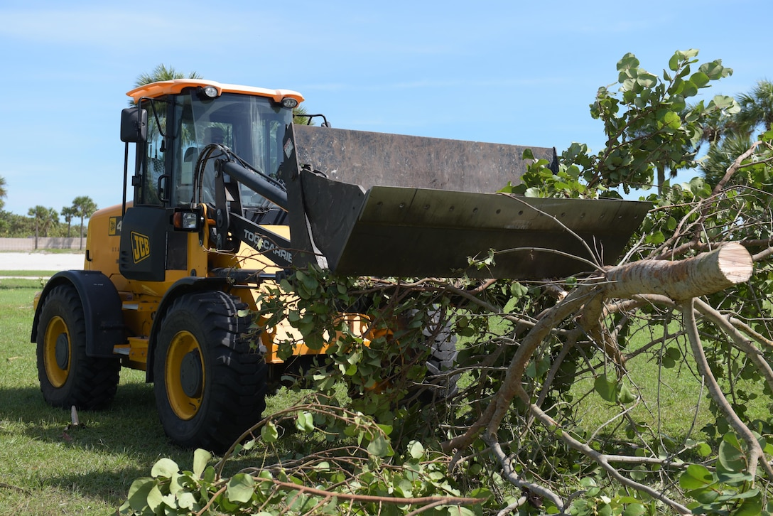 Tech. Sgt. Chad King, 45th Civil Engineer Squadron heavy equipment operator, collects debris during the 45th Space Wing's Hurricane Matthew recovery efforts Oct. 8, 2016, at Patrick Air Force Base, Fla. Hurricane Recovery Teams for Patrick AFB and Cape Canaveral Air Force Station deployed to an alternate location prior to the storm and remained on call to help with immediate assessment repair after the storm. (U.S. Air Force photo/Derwin Oviedo)