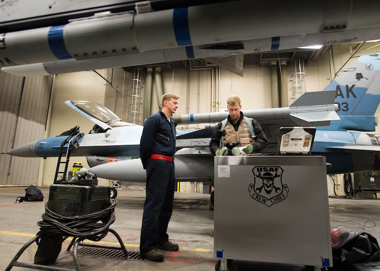 U.S. Air Force Airman 1st Class Spencer Hall, a 354th Aircraft Maintenance Squadron crew chief, briefs Col. David Mineau, the 354th Fighter Wing commander, on the maintenance records of the F-16 Fighting Falcon aircraft he prepares to fly for a sortie Oct. 10, 2016, during RED FLAG-Alaska (RF-A) 17-1 at Eielson Air Force Base, Alaska. The F-16 Fighting Falcon is a compact multi-role fighter aircraft, which the 18th Aggressor Squadron uses to simulate adversaries during RF-A. (U.S. Air Force photo by Staff Sgt. Shawn Nickel)