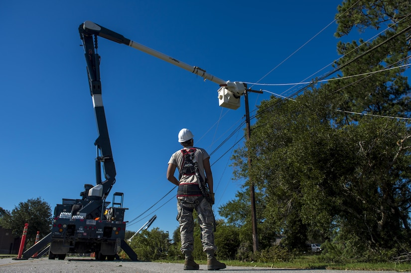 U.S. Air Force Senior Airmen Robert Aguilar and Casey Cooper, electrician linemen with the 628th Civil Engineer Squadron, repair electrical lines after  Hurricane Mathew swept through Joint Base Charleston, S.C., Oct. 9, 2016.  All non-essential personnel evacuated the area, but returned after disaster response coordinators assessed damage and verified a safe operating environment.