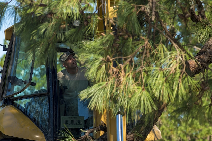 U.S. Air Force Master Sgt. Chris Moffett,  heavy equipment operator with the 628th Civil Engineer Squadron, tears down a broken tree limb after  Hurricane Mathew swept through Joint Base Charleston, S.C., Oct. 9, 2016. All non-essential personnel evacuated the area, but returned after disaster response coordinators assessed damage and verified a safe operating environment.