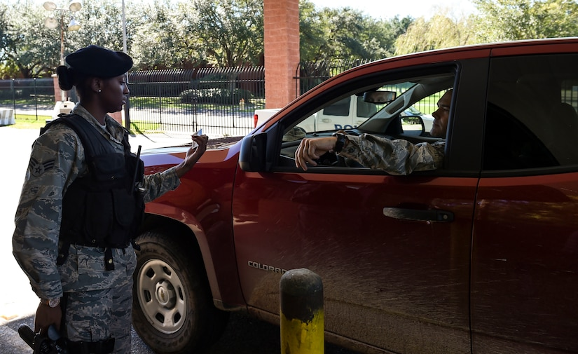 U.S. Air Force Senior Airman Jasmine Jamison, a patrol officer with the 628th Security Forces Squadron, checks the identification of those entering the gates after Hurricane Matthew swept the area on Joint Base Charleston - Naval Weapons Station, S.C., Oct. 9, 2016. All non-essential personnel evacuated the area, but returned after disaster response coordinators assessed damage and verified a safe operating environment.