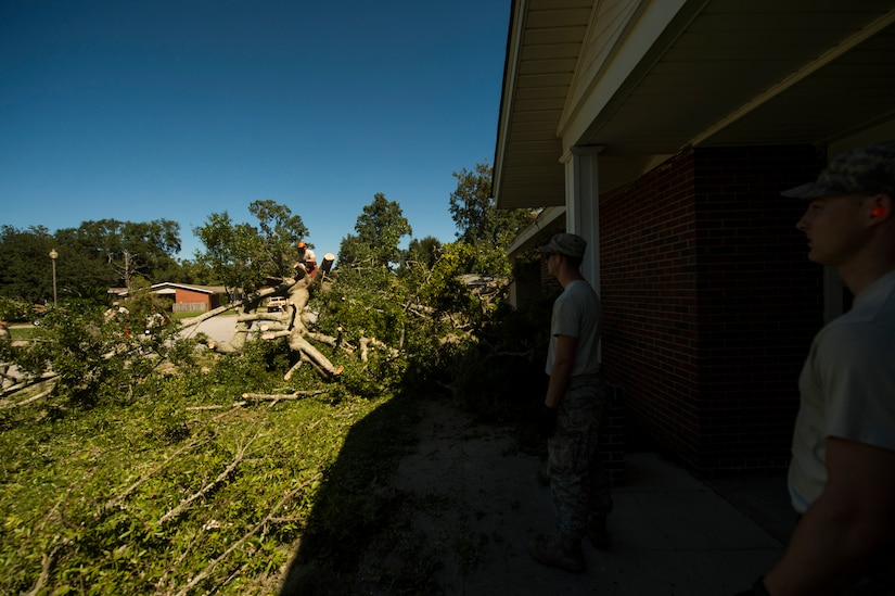 U.S. Air Force civil engineers with the 628th Civil Engineer Squadron remove fallen trees on Hunley Park-Air Base housing done by Hurricane Matthew on Joint Base Charleston, S.C., Oct. 9, 2016. All non-essential personnel evacuated the area, but returned after disaster response coordinators assessed damage and verified a safe operating environment.
