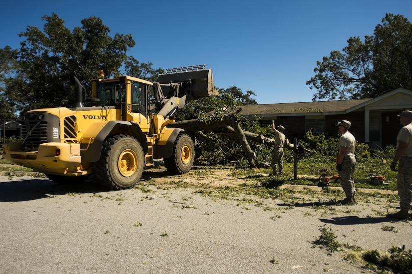 U.S. Air Force civil engineers with the 628th Civil Engineer Squadron use a front-end loader to remove fallen trees on Hunley Park-Air Base housing done by Hurricane Matthew on Joint Base Charleston, S.C., Oct. 9, 2016. All non-essential personnel evacuated the area, but returned after disaster response coordinators assessed damage and verified a safe operating environment.