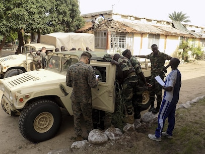 Cpl. Frank Cassella, a motor transport operator with Special Purpose Marine Air-Ground Task Force Crisis Response-Africa, shows the Gendarmerie Nationale Senegalaise a High Mobility Multipurpose Wheeled Vehicle (HMMWV) on Aug. 22, 2016, near Dakar, Senegal. On 2 August, 2016, the United States donated 23 HMMWVs to Senegal via the Excess Defense Articles (EDA) program. The HMMWVs will be used to support both Peace Keeping efforts abroad and to counter internal security issues, such as the transport of illicit materials across national borders. Recognizing that developing the skills needed to maintain older HMMWVs is just as important as having the equipment itself, planners from the United States and Senegal jointly developed a training program to pass these skills to Senegalese mechanics. This engagement was the first in a series of planned courses of instruction meant to achieve the goal of developing a cadre of Senegalese HMMWV technicians. (U.S. Marine Corps courtesy photo/released)