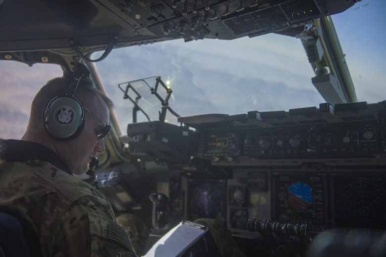 A U.S. Air Force C-17 Globemaster III pilot looks at his notes during a transport mission in support of Operation Freedom Sentinel in Southwest Asia Sept. 30, 2016. The C-17 is the newest most flexible cargo aircraft to enter the airlift force. The C-17 is capable of rapid strategic delivery of troops and all types of cargo to main operating bases or directly to forward bases in the deployment area. (U.S. Air Force photo by Staff Sgt. Douglas Ellis/Released)
