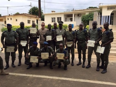 The Gendarmerie Nationale Senegalaise soldiers hold their graduation diplomas with 1st Lt. Connor Smithson, a Theater Security Cooperation commander, following graduation near Dakar, Senegal, Aug. 26, 2016.  Marines with Special Purpose Marine Air-Ground Task Force Crisis Response-Africa trained with the Senegalese Gendarmerie during a partner-nation exercise.  (U.S. Marine Corps courtesy photo/released)