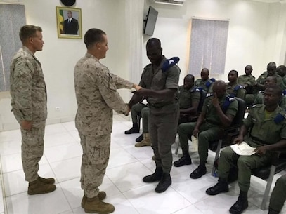 1st Lt. Connor Smithson, a Theater Security Cooperation commander with Special Purpose Marine Air-Ground Task Force Crisis Response-Africa, hands out diplomas to the graduating Gendarmerie Nationale Senegalaise for completing their course near Dakar, Senegal, Aug. 26, 2016.  Establishing entry control points, checking vehicles and searching personnel were points of focus during the partner nation exercise designed to counter illicit activity. (U.S. Marine Corps courtesy photo/released)