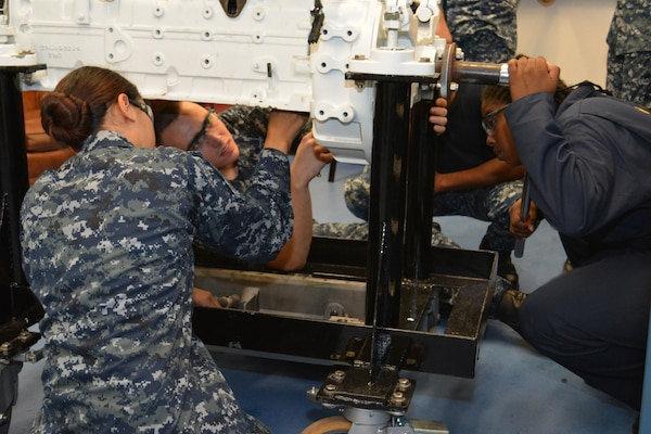 Petty Officer 1st Class Staci Allen (Right) slowly turns the crankshaft as Seaman Jacob Pruitt (Center) and Seaman Hannah Ybarra check the clearance inside the cylinder on a marine diesel engine. Sailors in the Diesel Shop at SERMC repair or replace valves, pumps, compressors and control devices used with diesel engines.