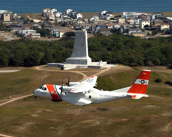 An HC-144A Medium Range Maritime Patrol Aircraft flies past the Wright Brothers National Memorial in Kitty Hawk, North Carolina. (U.S. Coast Guard Photo by Dave Silva)