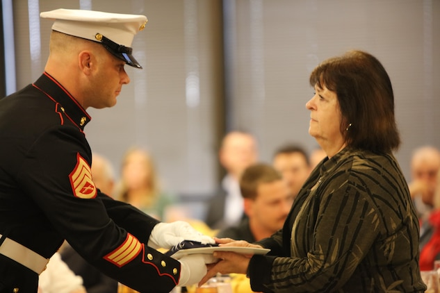 """Staff Sgt. Christian Wolanski, a recruiter at Recruiting Station St. Louis, delivers a flag to a Gold Star mother at the 7th Annual Gold Star Family Luncheon on Oct. 1, 2016 in St. Louis, Mo. The term """"Gold Star"""" refers to a family who lost a loved one in war. (U.S. Marine Corps photo by Cpl. Jennifer Webster/Released)"""