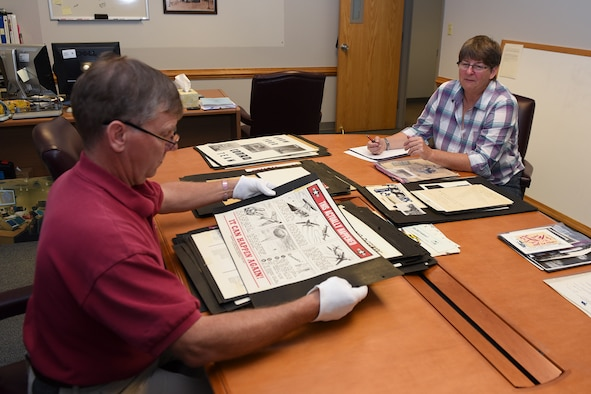PETERSON AIR FORCE BASE, Colo. – Jeffrey Nash, Peterson Air and Space Museum assistant director, and Gail Whalen, Peterson Air and Space Museum director, inventory a potential donation of graphic works at Peterson Air Force Base, Colo., Oct. 3, 2016. The graphic was created by Paul S. Jaffe, who was the lead graphic artist and cartoonist for the Air Defense Command and North American Aerospace Defense Command in the 1950s and early 60s.  Jaffe designed the original NORAD emblem that is still used today. (U.S. Air Force photo by Philip Carter)