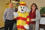 Sparky poses with Defense Logistics Agency Aviation Command Support Directorate employees, Maurice Sanabria, Command Programs Office chief; and Cathy Hopkins, public affairs specialist, while visiting offices on Defense Supply Center Richmond, Virginia, Oct. 11 to spread the word to check smoke alarms during Fire Prevention Week, Oct. 9-15, 2016.