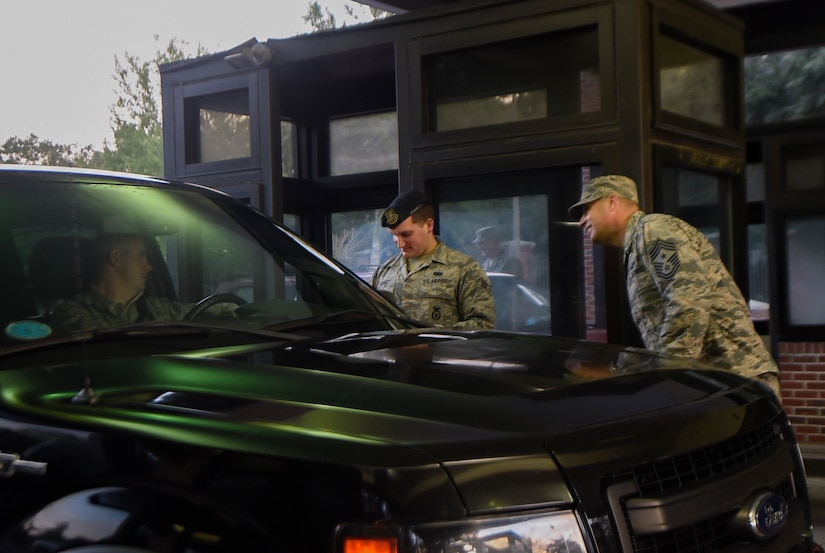 Senior Airman Hunter Banks, 628th Security Forces Squadron gate guard, and Chief Master Sgt. Todd Cole, 628th Air Base Wing command chief, welcome JB Charleston personnel entering the base, Oct. 11, 2016. Base leadership welcomed members back after the installation evacuated Oct. 5 due to Hurricane Matthew.