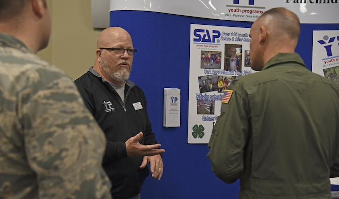 John Smith, 92nd Force Support Squadron youth programs director, discusses the impact of Fairchild's youth programs with Col. Ryan Samuelson, 92nd Air Refueling Wing commander, during the Combined Federal Campaign Charity Fair Oct. 7, 2016, at the Red Morgan Center. The fair hosted six charities from the local area to encourage participation regardless of the monetary contribution amount. (U.S. Air Force photo/Senior Airman Mackenzie Richardson)
