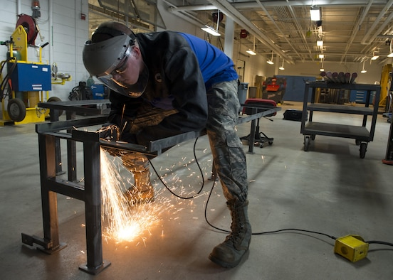 Senior Airman Cory Swan, 512th Maintenance Squadron metals technician, uses an angle grinder to remove a piece of metal from a metal frame Sept. 19, 2016, at Dover Air Force Base, Del. The Metals Technology Shop supported the Air Force Mortuary Affairs Operations mission by designing and building frames for their new transfer vehicles. (U.S. Air Force photo by Senior Airman Zachary Cacicia)