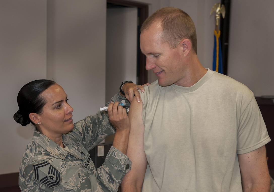 Maj. Aaron Drenth, Armament Directorate, receives his influenza vaccine from Senior Master Sgt. Melanie Collins, 96th Medical Group, at Eglin Air Force Base, Fla. Oct. 11.  The flu shots are being administered this week during the 2016 mass influenza vaccine campaign at the 413th Flight Test Squadron headquarters, Bldg. 439. (U.S. Air Force photo/Kevin Gaddie)