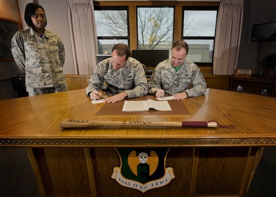 (From left) Tech Sgt. Cornelia Justice, 5th Bomb Wing staff judge advocate NCO in charge of military justice and Combined Federal Campaign representative, watches Col. Matthew Brooks, 5th BW commander, and Chief Master Sgt. Paul Elliott, 5th BW command chief, donate to the Combined Federal Campaign at Minot Air Force Base, N.D., Oct. 7, 2016. In 2015, the total amount contributed by both military and civilian donors in Minot AFB was $110,000. This year, Team Minot's campaign runs until Oct. 22, 2016, with a goal of $125,000. (U.S. Air Force photo/Airman 1st Class J.T. Armstrong)