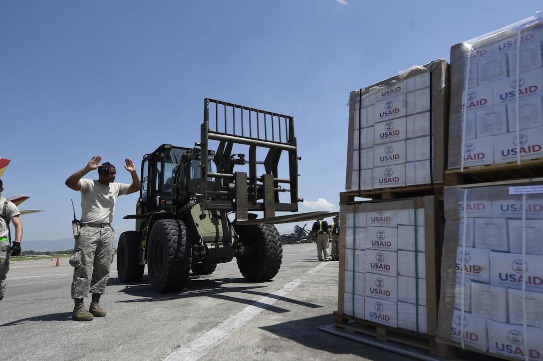 Tech. Sgt. Ronald Rowe, 621st Contingency Response Wing, facilitates transport of USAID food and provisions for Hurricane victims in Haiti, October 9th, 2016, Port-Au-Prince, Haiti. The CRW has units ready to deploy anywhere in the world in support of emergency operations, within 12 hours of notification.(U.S. Air Force photo by Staff Sgt. Robert Waggoner/released)