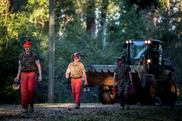 Marines carry equipment and fuel to clear debris on a road aboard Marine Corps Air Station Beaufort Oct. 9. Marines and sailors with MCAS Beaufort continued to work to remove debris and establish infrastructure aboard the air station and Laurel Bay after Hurricane Matthew.