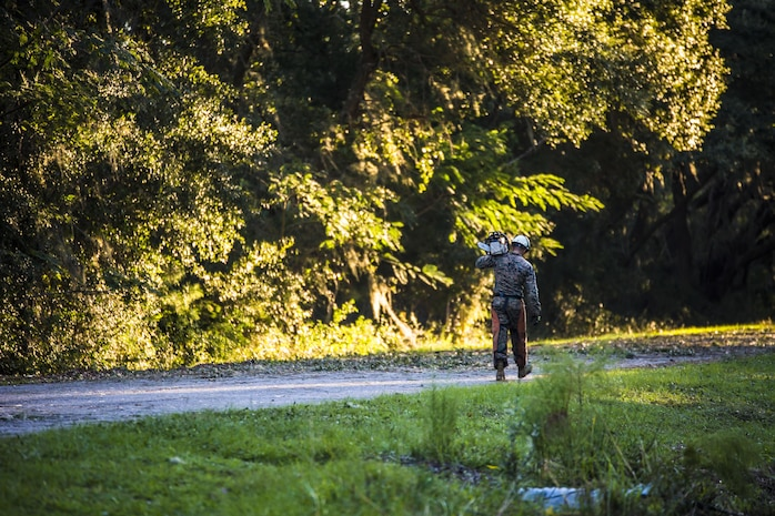 A Marine carries a chainsaw to help remove a tree on a road aboard Marine Corps Air Staiton Beaufort Oct. 9. Marines and sailors with MCAS Beaufort continued to work to remove debris and establish infrastructure aboard the air station and Laurel Bay after Hurricane Matthew.