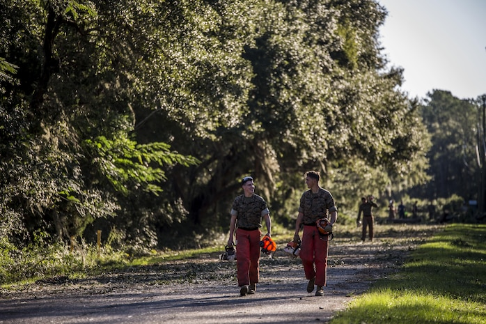 Marines carry equipment and gear after cutting down trees on a road aboard Marine Corps Air Station Beaufort Oct. 9. Marines and sailors with MCAS Beaufort continued to work to remove debris and establish infrastructure aboard the air station and Laurel Bay after Hurricane Matthew.