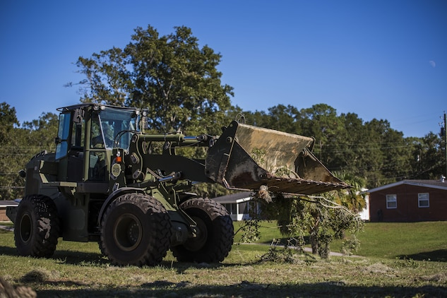 A Marine uses heavy equipment to remove a fallen tree from a backyard aboard Laure Bay Oct. 9. Marines and sailors with Marine Corps Air Station Beaufort continued to work to remove debris and establish infrastructure aboard the air station and Laurel Bay after Hurricane Matthew.