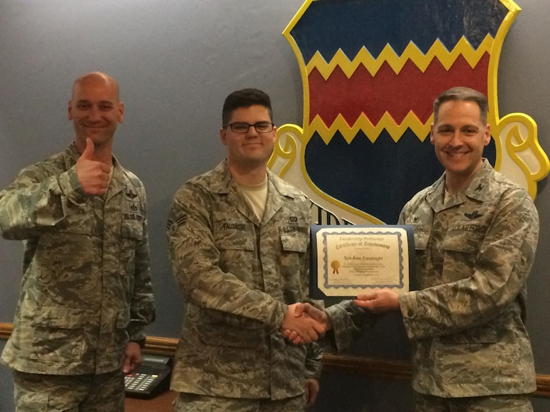 Air Force Col. Joseph Santucci, 55th Operations Group commander (right) and Air Force Chief Master Sgt. Michael Rager, 55th Operations Group command chief (left), present Air Force Senior Airman Alex Fausnight, 338th Combat Training Squadron (center), with his Gold Level certificate for Leadership Pathways. Leadership Pathways is an Air Force program that Air Combat Command has adopted to help support the Comprehensive Airmen Fitness strategy. (Courtesy Photo)