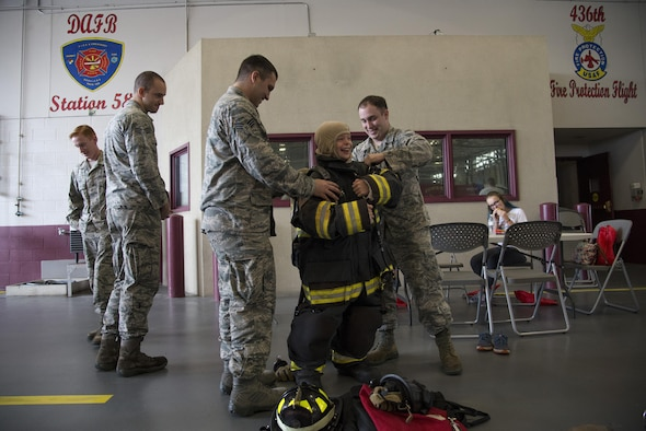 Senior Airmen James Marker and Jamie Perigny, 436th Civil Engineer Squadron firefighters, help Merric Hunt, son of Master Sgt. Adam Hunt, 436th Maintenance Squadron Isochronal Maintenance Dock chief, try on firefighting bunker gear during the Dover Air Force Base First Responders' Special Needs Day Oct. 8, 2016, at the 436th CES Fire Department on Dover AFB, Del. Event attendees had the opportunity to try on equipment, tour emergency response vehicles and learn something new about first responders. (U.S. Air Force photo by Senior Airman Aaron J. Jenne)