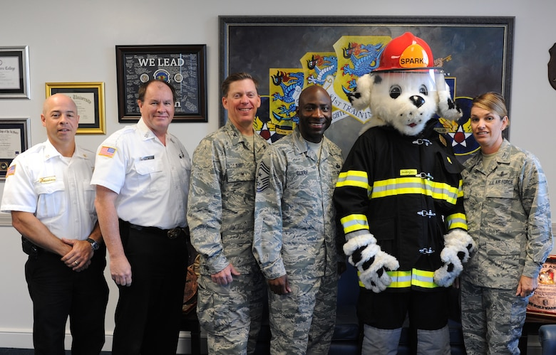 Sparky the Fire Dog poses for a photo with 81st Training Wing leadership and Keesler Fire Department members at the 81st TRW headquarters building to kick off Fire Prevention Week Oct. 11, 2016, on Keesler Air Force Base, Miss. The weeklong event includes fire drills, literature hand-outs and stove fire demonstrations around the base and concludes with an open house at the fire department Oct. 15. (U.S. Air Force photo by Kemberly Groue/Released)