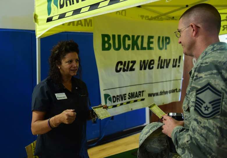 A Drive Smart Colorado team member discusses seat belt safety with Senior Master Sgt. Kristopher Coats, 460th Comptroller Squadron superintendent, during a Safety Day event Oct. 7, 2016, at the fitness center on Buckley Air Force Base, Colo. Drive Smart Colorado, a program designed to reduce the number of traffic crashes through community collaboration and education, provided information on their different programs to Team Buckley during the daylong event. (U.S. Air Force photo by Airman 1st Class Gabrielle Spradling/Released)