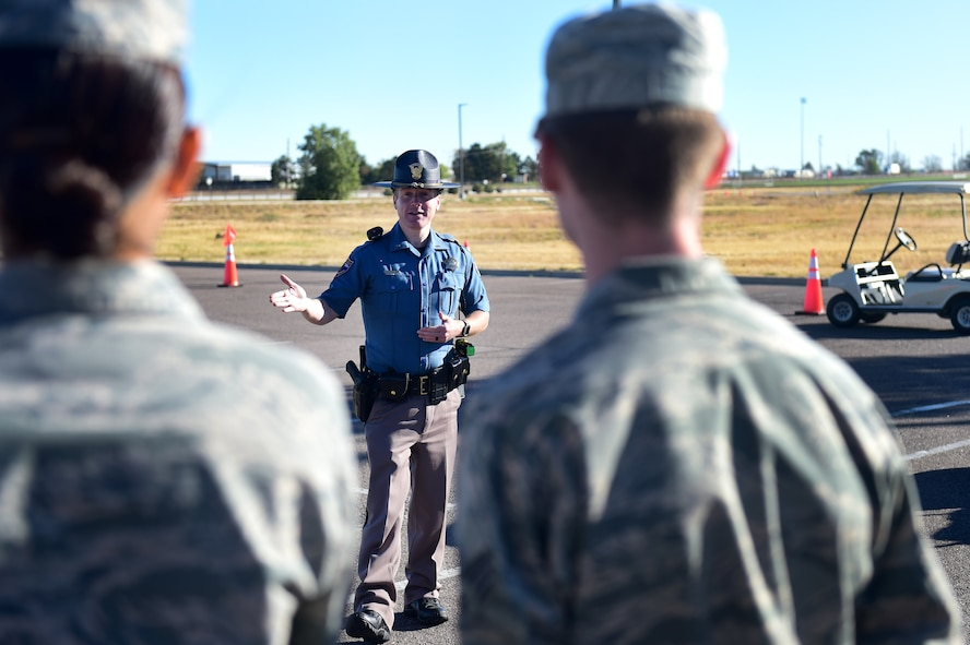 Josh Lewis, Colorado State Trooper, explains the process of a field sobriety test to Team Buckley members during a Safety Day event Oct. 7, 2016, at the fitness center on Buckley Air Force Base, Colo. The hands-on portions of the event included four alcohol-impairment obstacles courses, two field sobriety stations, child seat safety station, motorcycle safety station, experienced driver station, marijuana impairment station, semi-truck blind spot demonstration, a wrecked car from a DUI, and a hunting and outdoor station. (U.S. Air Force photo by Airman 1st Class Gabrielle Spradling/Released)