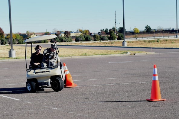 A member of Team Buckley tries to drive a golf cart while wearing drunk goggles during a Safety Day event Oct. 7, 2016, at the fitness center on Buckley Air Force Base, Colo. The event included hunting and outdoor safety, home and fire safety and hands-on activities for driving safety. (U.S. Air Force photo by Airman 1st Class Gabrielle Spradling/Released)