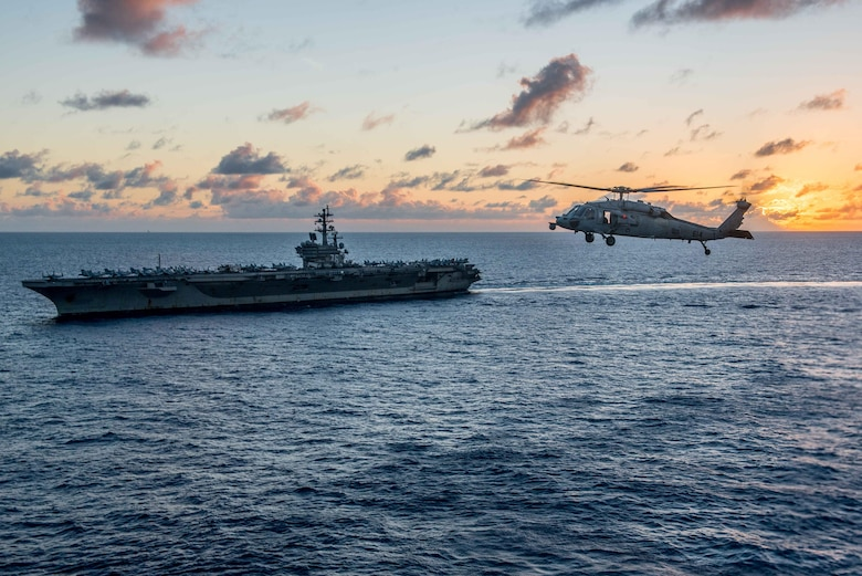 """PHILIPPINE SEA (Oct. 7, 2016) - An MH-60S Sea Hawk, assigned to the """"Golden Falcons"""" of Helicopter Sea Combat Squadron (HSC) 12, flies near the Navy's only forward-deployed aircraft carrier, USS Ronald Reagan (CVN 76), following helicopter search-and-rescue training. This training enables real-world proficiency in open-ocean rescue procedure and equipment. Ronald Reagan, the Carrier Strike Group Five (CSG 5) flagship, is on patrol supporting security and stability in the Indo-Asia-Pacific region."""
