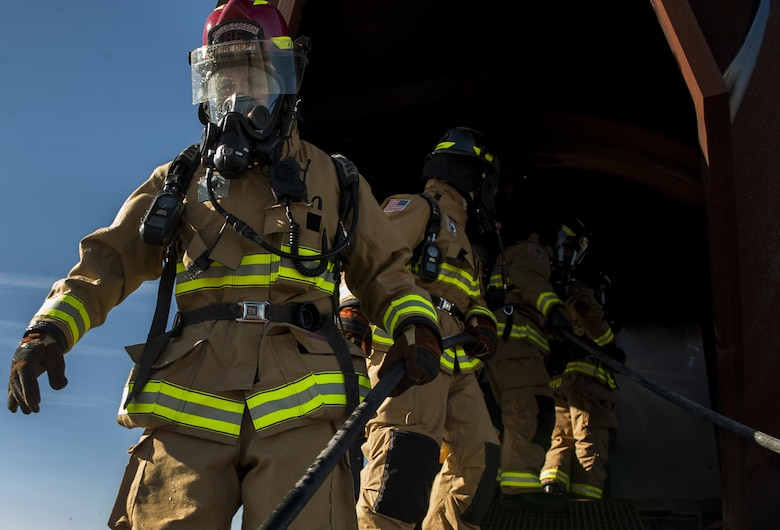 Firefighters, assigned to the 99th Civil Engineer Squadron Fire Protection Flight, exit a mock shell of an aircraft after putting out controlled fires at Nellis Air Force Base, Nev., Oct. 6, 2016. On Wednesday, Oct. 12, NCFD will be at the Child Development Centers from 9 a.m. to 10:30 a.m. with a Fire Truck and Sparky the Fire Dog. (U.S. Air Force photo by Airman 1st Class Kevin Tanenbaum/Released)