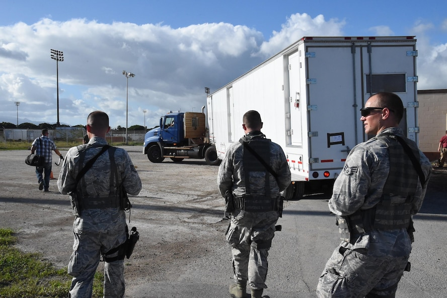 Staff Sgt. Ryan Ernst, Staff Sgt. Jefrey Davis, and Senior Airman Hans Houser, 4th Space Operations Squadron mobile team, escort the Advanced Ground Mobile space operating semitrailer to the Hawaii exercise operating location. Mobile team members are required to be trained and weapons qualified to defend the assets in contingency situations. (U.S. Air Force photo/2nd Lt. Darren Domingo)